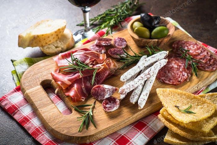 Antipasto delicatessen - sliced meat, ham, salami, olives on wooden board