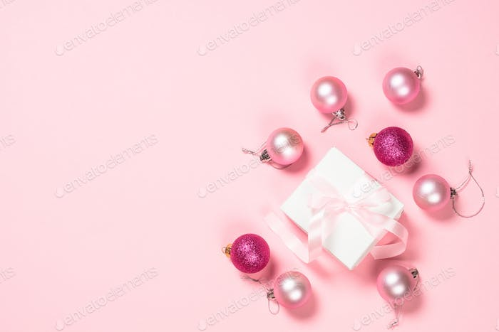 Christmas flat lay background with christmas present and decorations on pink.