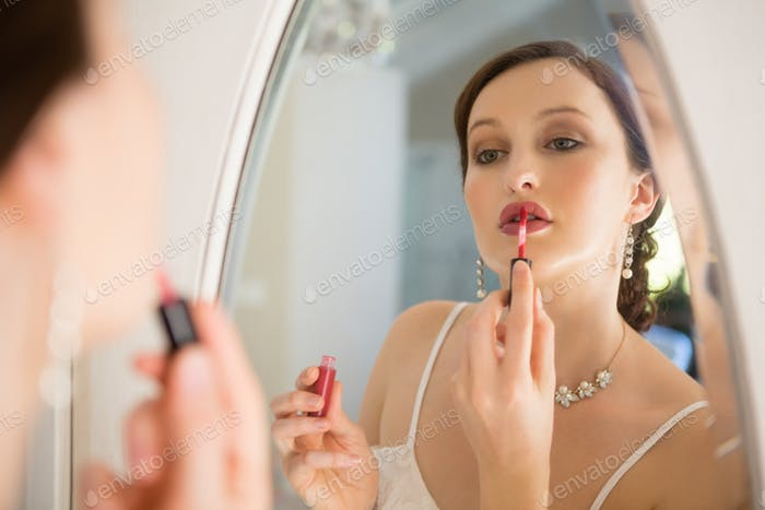 Side view of beautiful bride applying lip gloss reflecting on mirror