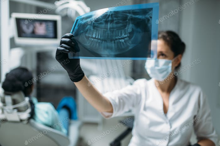 Dentist looking on x-ray picture, dental clinic