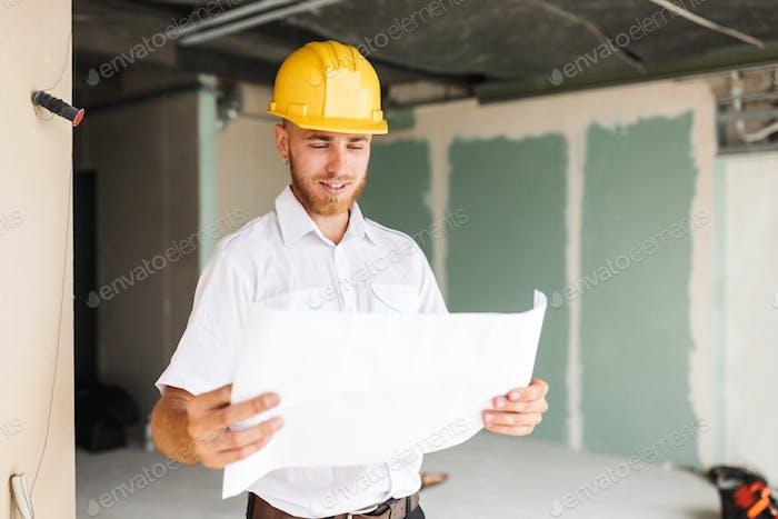 Junger Architekt in weißem Hemd und gelben Hardhut glücklich suchen