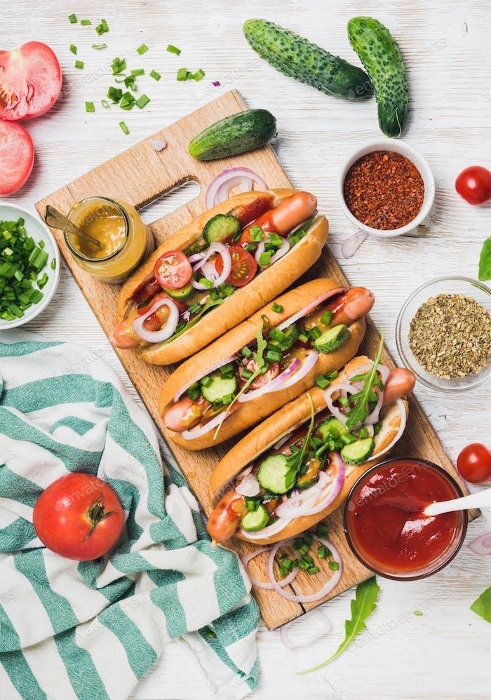 Hausgemachte Hot-Dogs mit frischem Gemüse und Gewürzen auf weißem Hintergrund