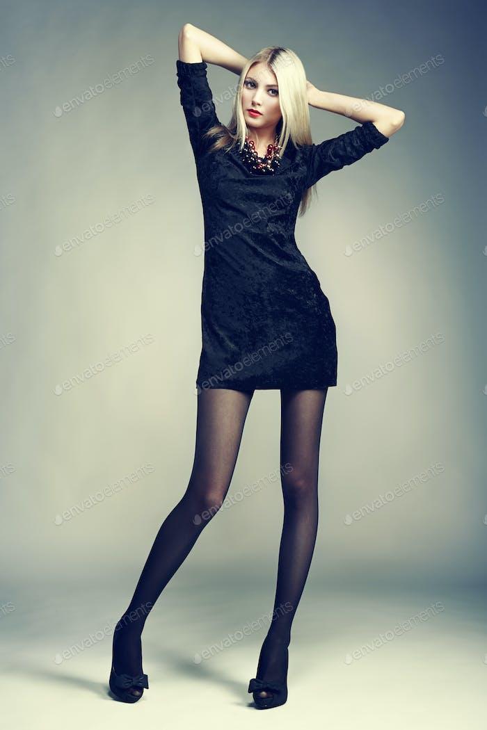 Photo of beautiful blonde woman in black dress