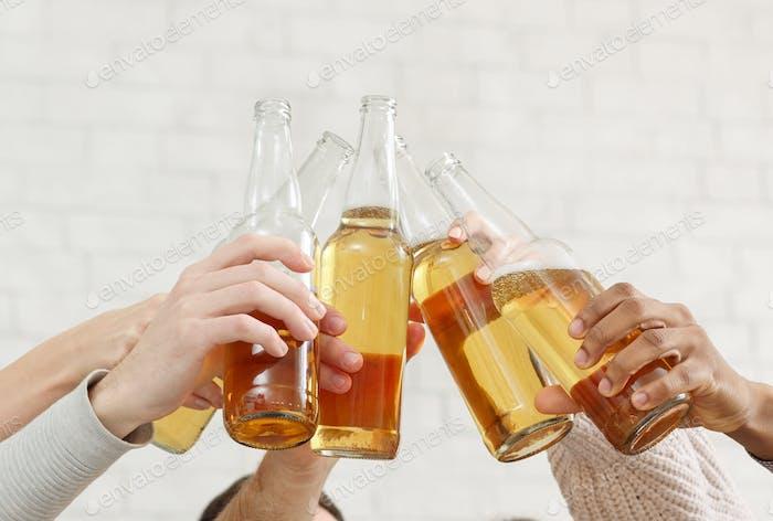 Fiesta Página de inicio. Amigos tintineando botellas de cerveza en Página de inicio