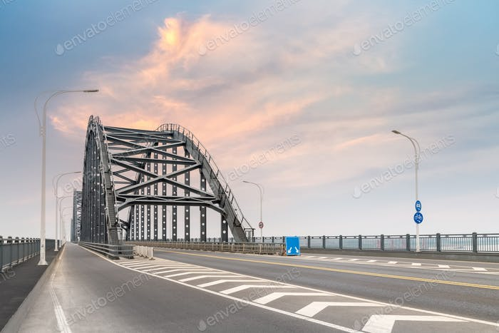 steel bridge and road with sunset sky