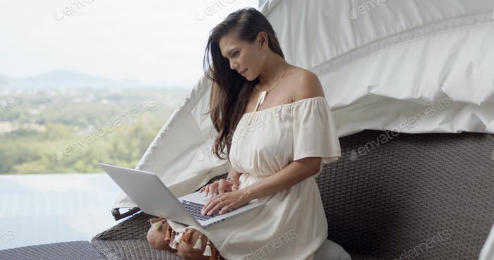 Relaxed woman using laptop on terrace against beautiful landscape