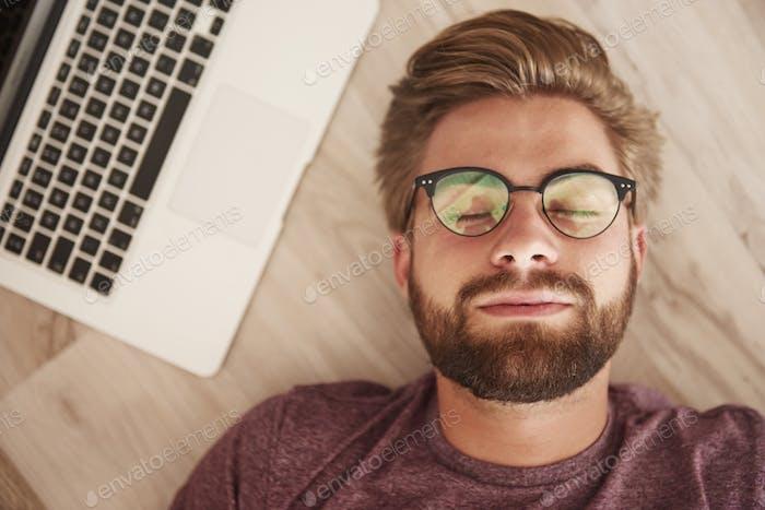 Schlafender Mann mit Laptop neben Gesicht