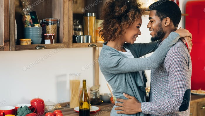 Lovely black couple embracing in cozy kitchen