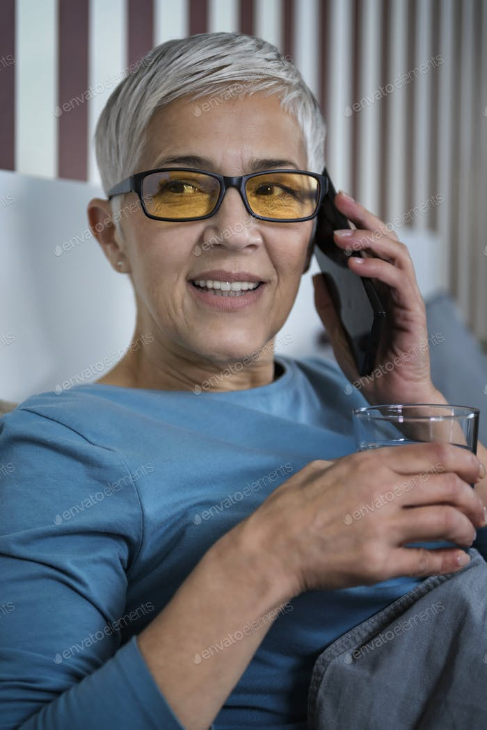 Blue-Light Blocking Glasses. Mature Woman Talking over the Phone