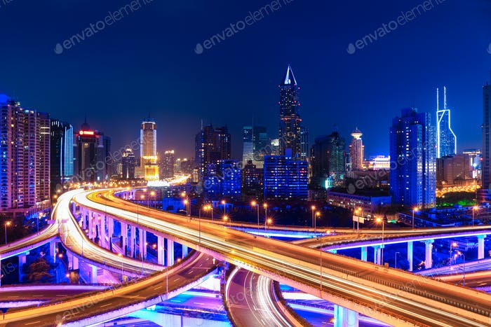 modern city skyline with interchange overpass at night