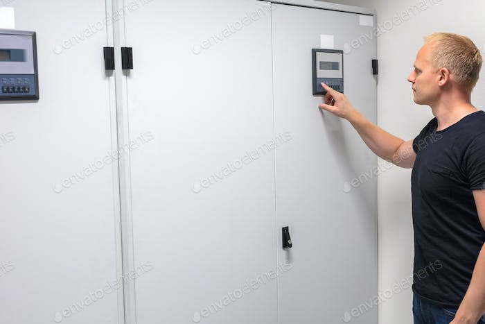 Male Technician Adjusting Air Conditioner In Datacenter