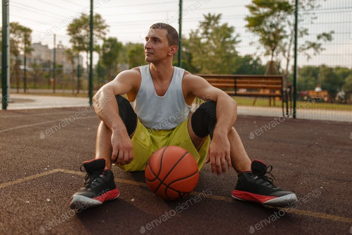 Basketball player sitting on the ground outdoor
