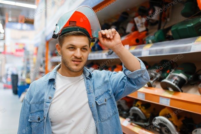 Comprador masculino tratando de una máscara en ferretería