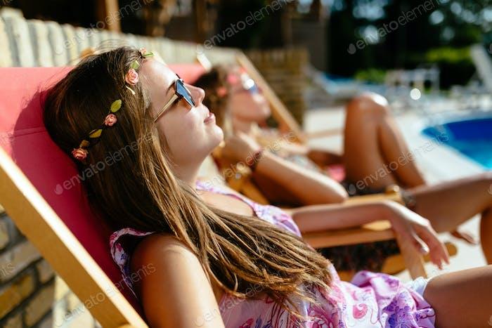 Girls enjoying summer vacation in chairs