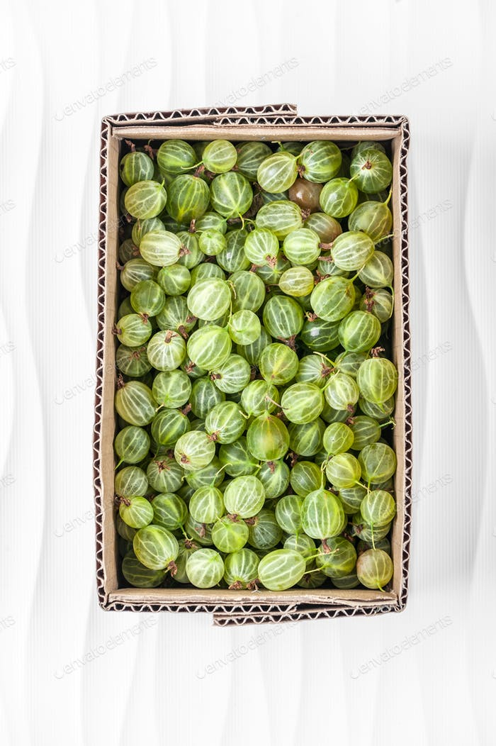 Gooseberries in a cardboard box on a white textured background.
