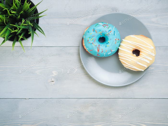 donuts on gray wooden background , copy space, top view