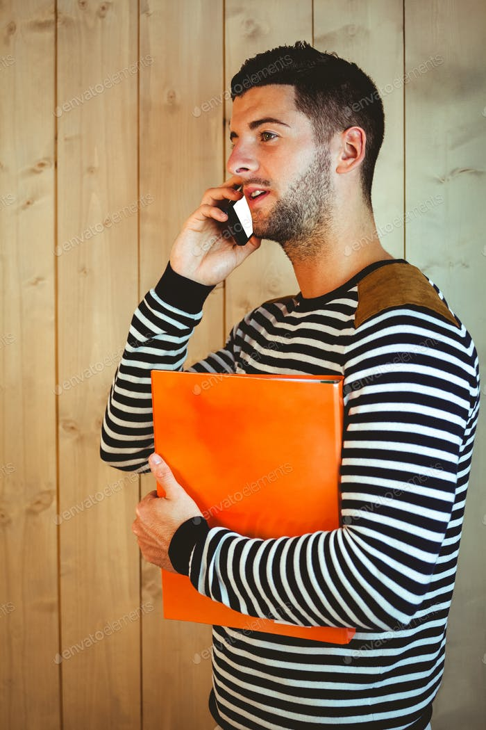 Casual hipster using his phone on wooden background