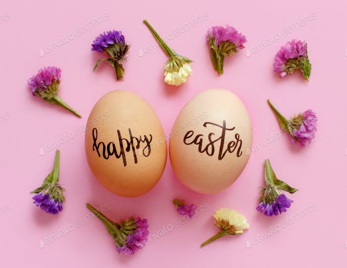 Eggs with inscription HAPPY EASTER and small flowers over light pink background