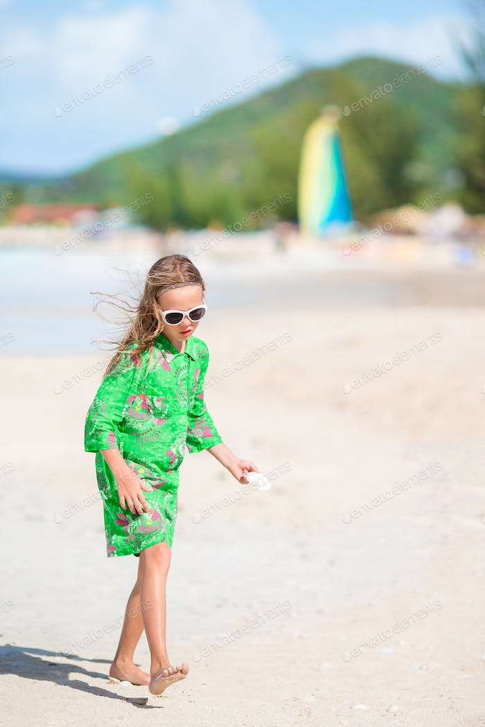 Little cute girl with seashell in hands at tropical beach. Adorable little girl playing with