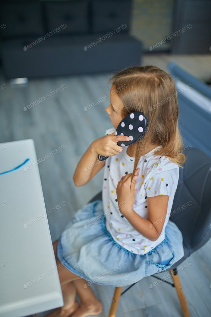 Pretty Little girl combing by herself hair in front of a mirror