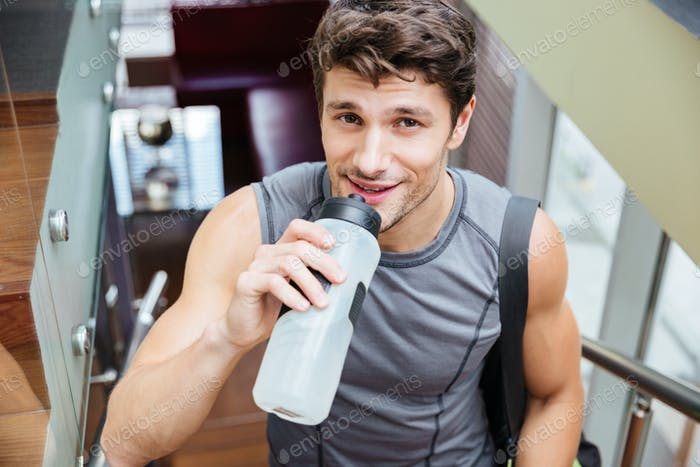 Smiling man athlete walking and drinking water in gym