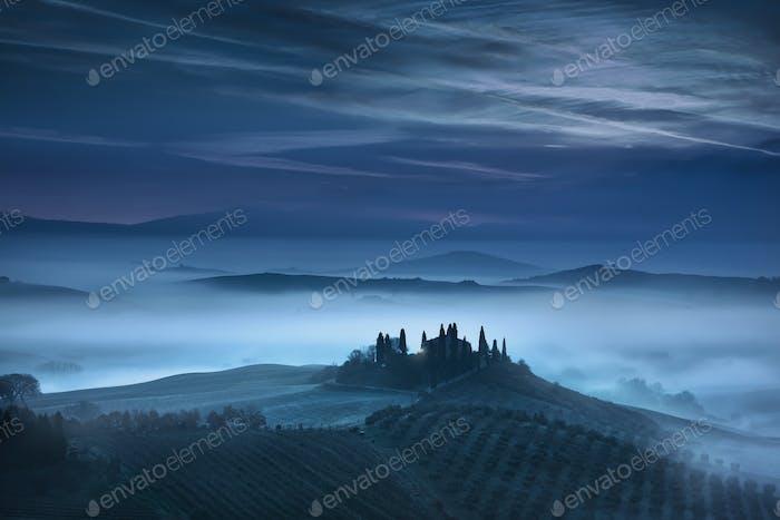 Tuscany blue foggy morning, farmland and cypress trees. Italy.