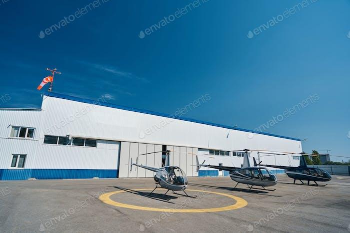 Three stylish empty rotorcrafts on landing pad