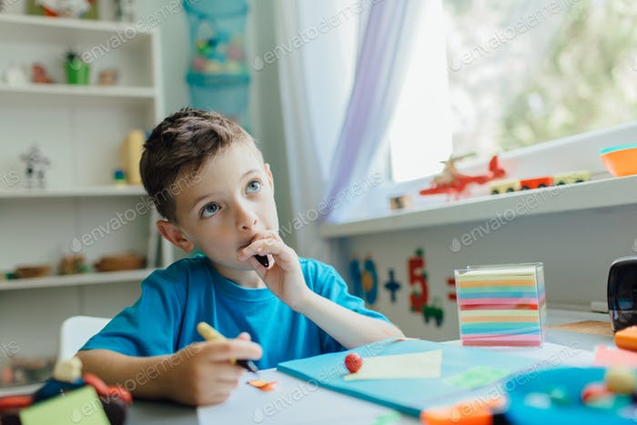 Thinking student doing his homework at home