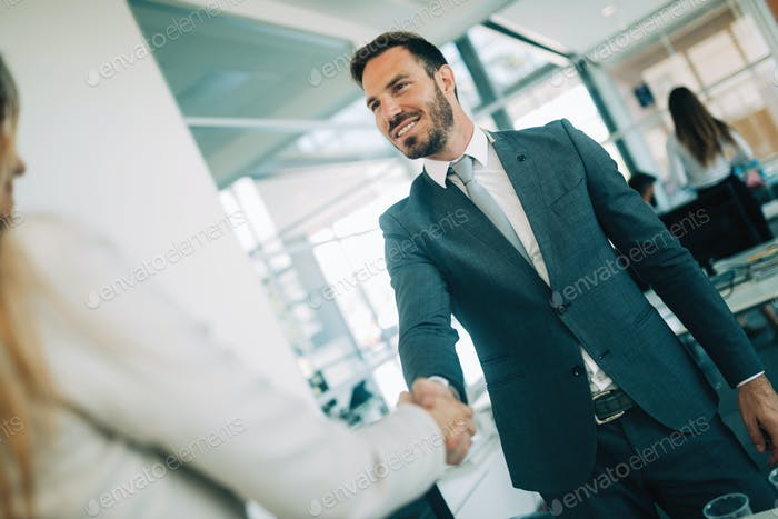 Young businessman and woman shake hands as hello in office portrait