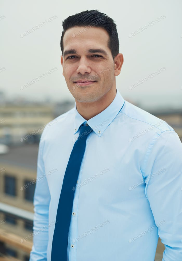 Young handsome Hispanic man on a rooftop