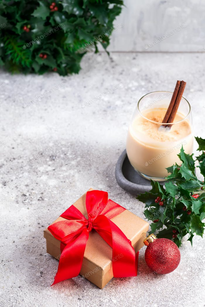 Winter spicy hot drink eggnog in a glass with cinamon and gift box on light stone table