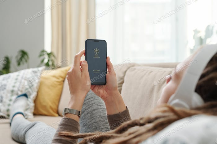 Hands of young restful woman holding smartphone in front of herself