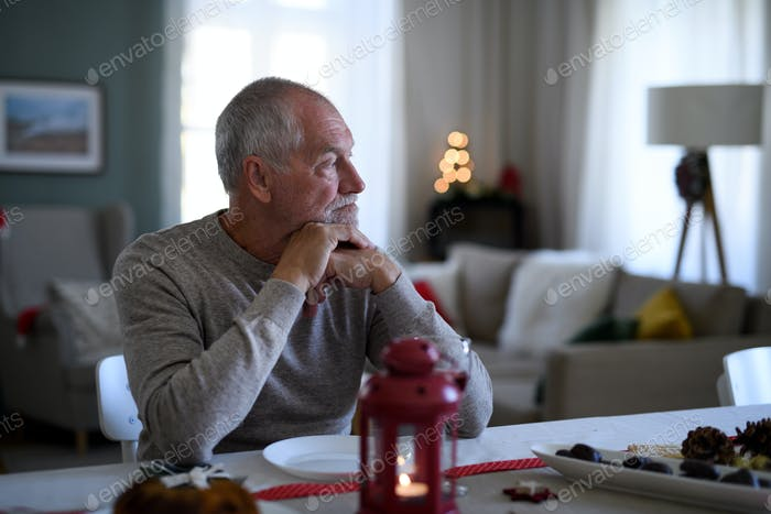 Lonely senior man sitting at the table indoors at Christmas, solitude concept