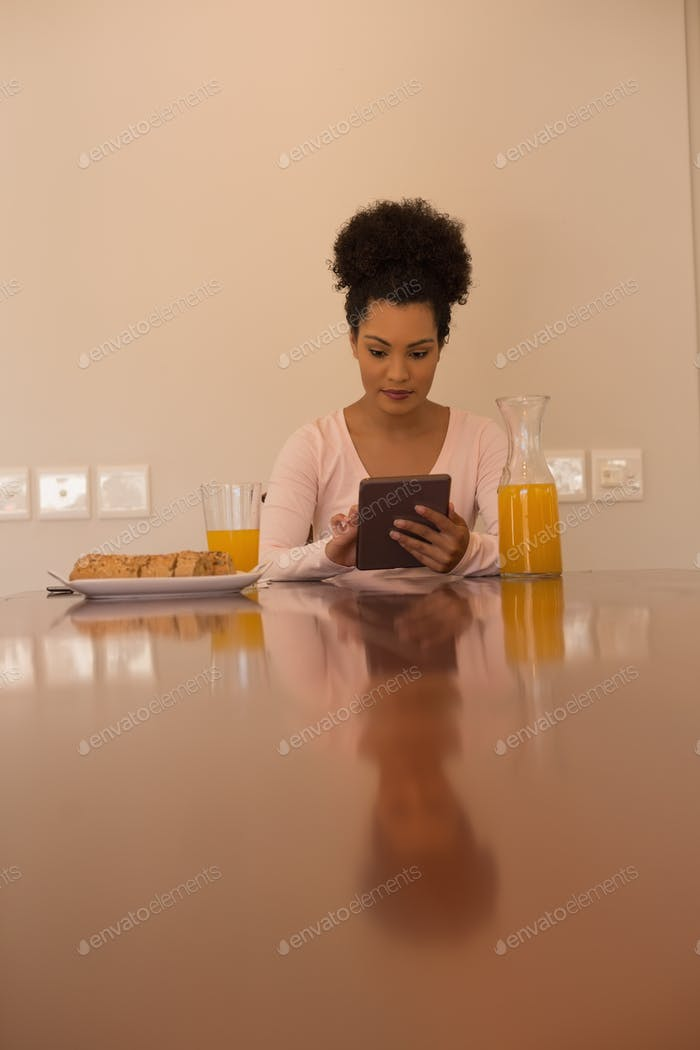 Front view of African American beautiful woman using digital tablet at home during a breakfast