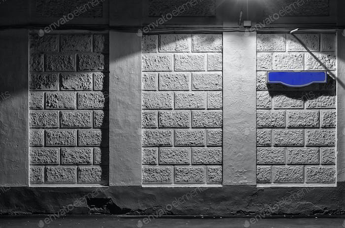 Wall of an building with a blank blue sign for the street name