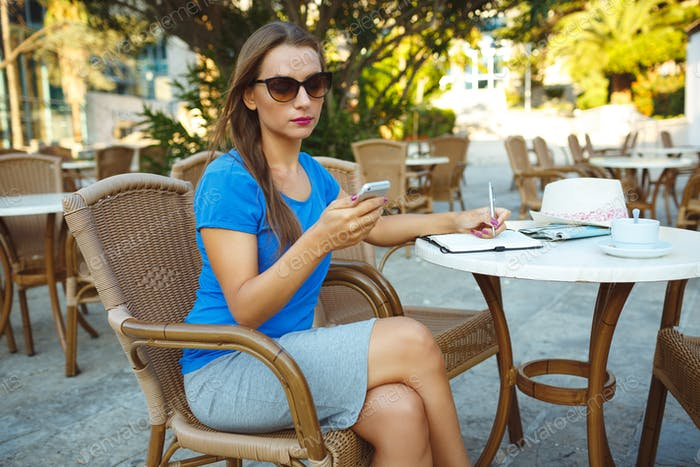 Young pretty woman using smartphone and makes notes in a noteboo