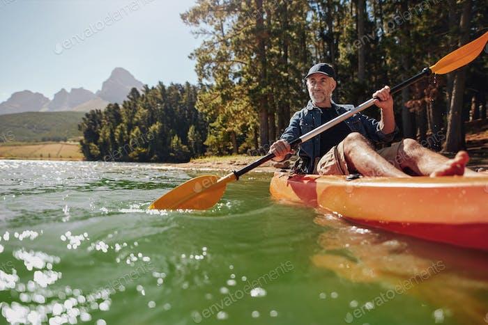 Reifer Mann mit genießen Kajakfahren in einem See