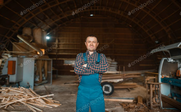 Woodworker in uniform at his workplace, lumbermill