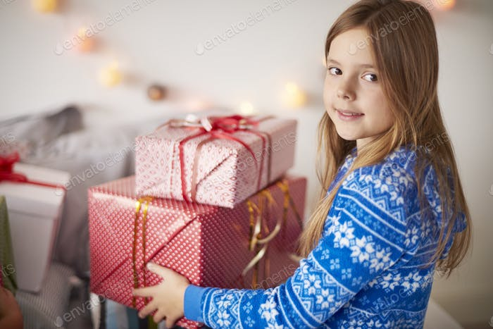 Cute girl holding stock of Christmas presents