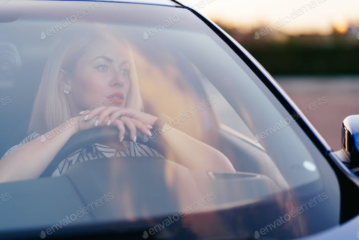 Woman driving a car, view through front window