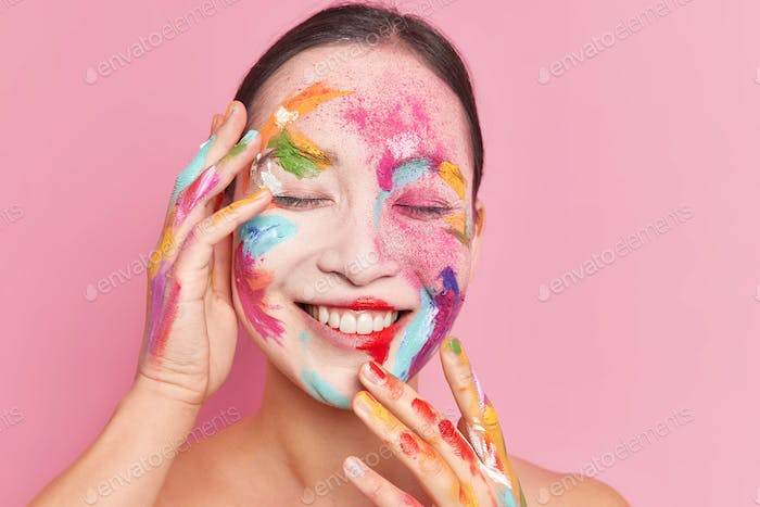 Close up shot of happy female model closes eyes and touches face gently smeared wit colorful waterco