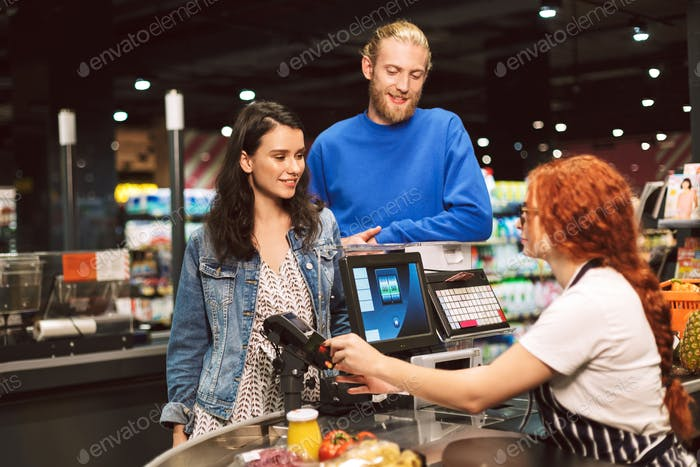 Beautiful smiling couple standing near cashier desk while happil