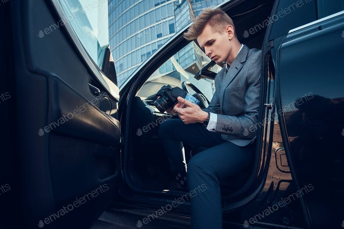 Young buisnisman is looking to his mobile phone while sitting in the car.