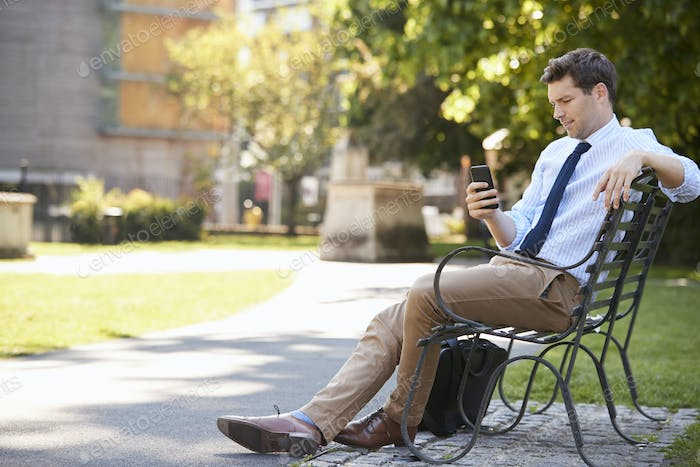 Businessman Outdoors Using Mobile Phone On Lunch Break In Park