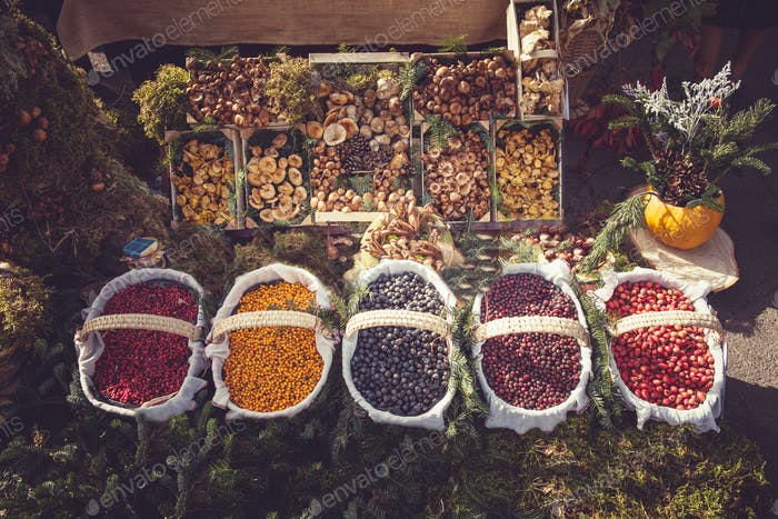 Different types of mountain fruits and mushrooms in baskets in the market. Autumn harvesting