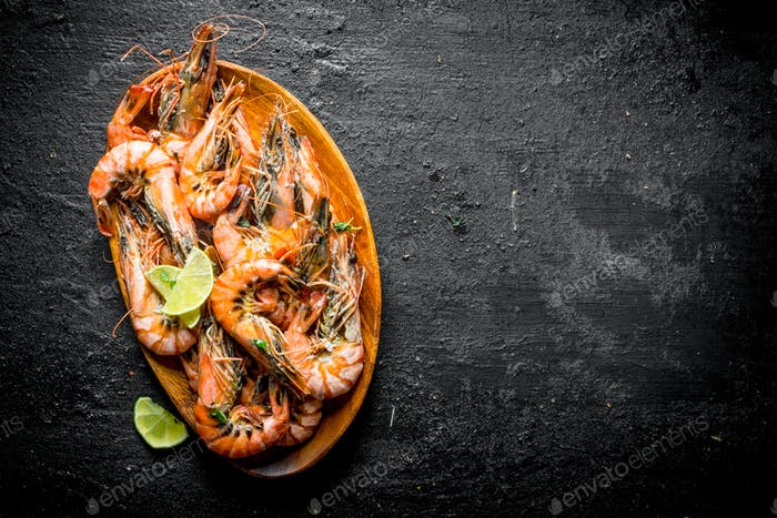 Boiled shrimps on a wooden plate with chopped lime.