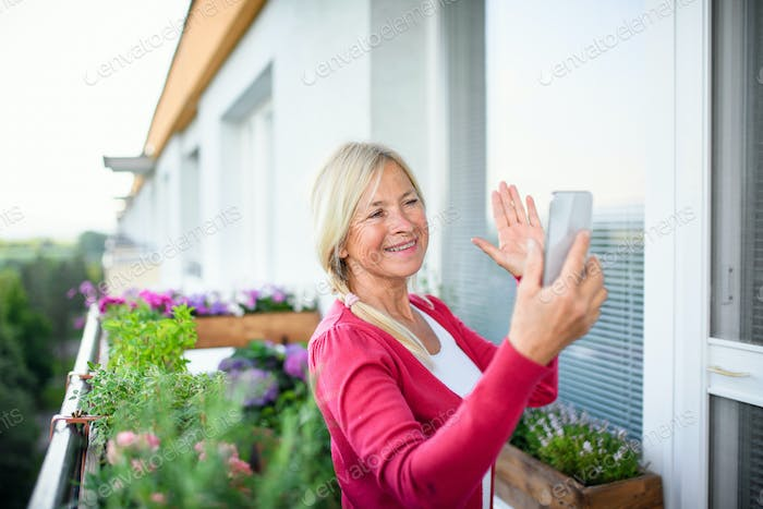 Senior woman with smartphone relaxing on balcony in summer, video call concept