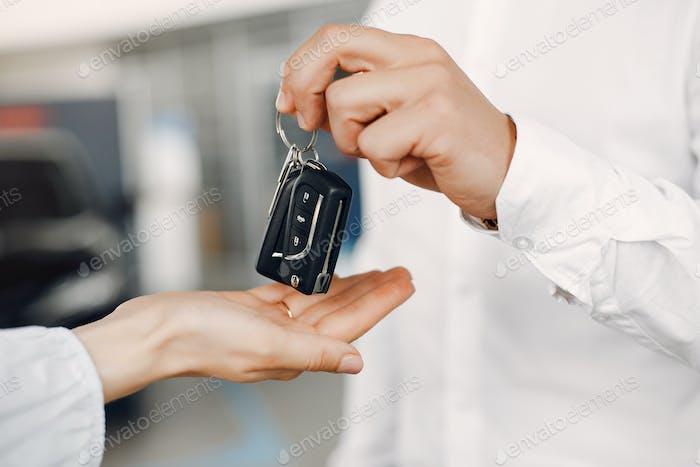 Stylish and elegant couple in a car salon