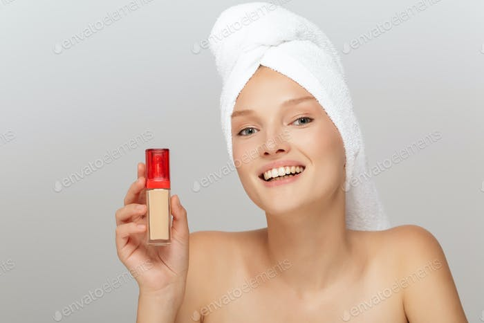 Portrait of young joyful woman without makeup with white towel o