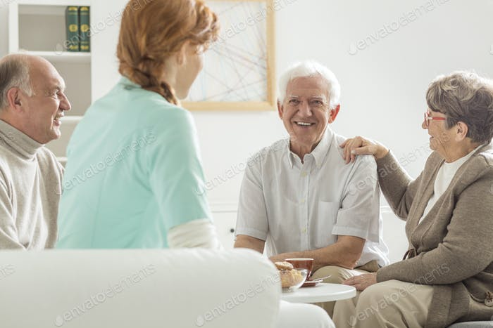 Seniors sitting with nurse